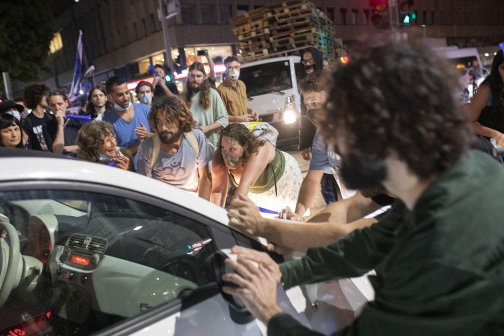 מפגינים חוסמים את רחוב אבן גבירול במהלך מחאה נגד ״חוק הקורונה״ בתל אביב (צילום אורן זיו)