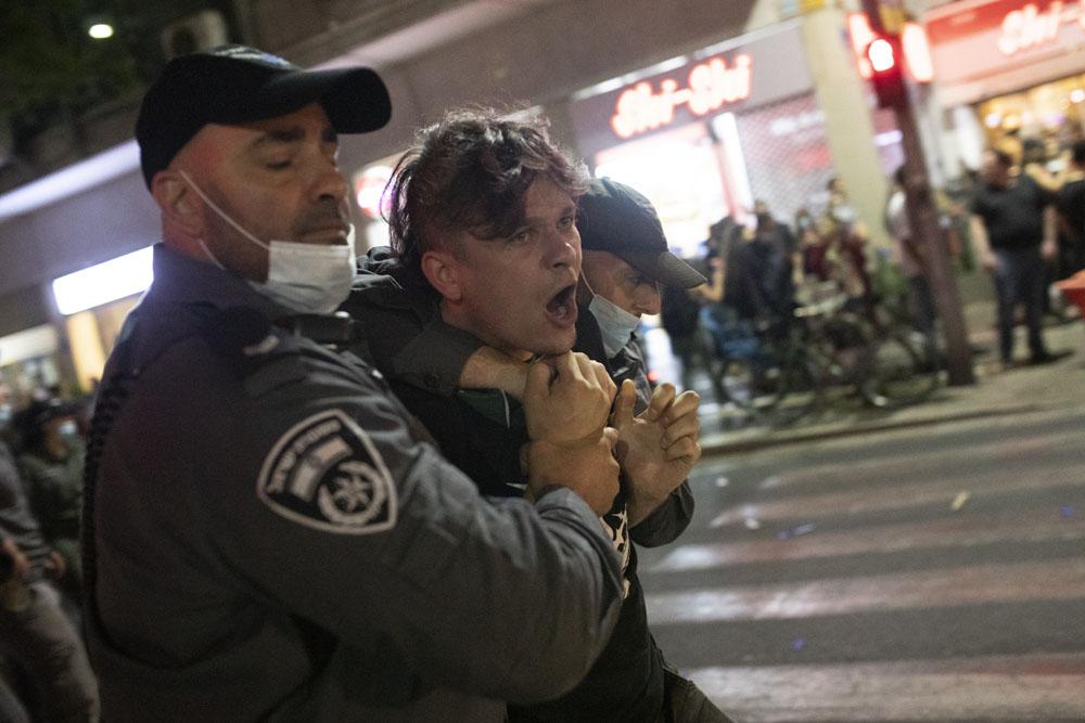 שטורים עוצרים מפגין במהלך מחאה נגד ״חוק הקורונה״ בתל אביב (צילום אורן זיו)