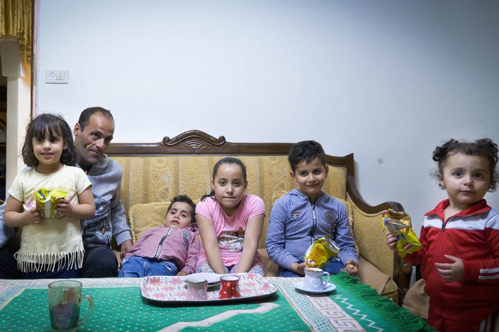 משפחת אבו דיאב בסלון של אחיו של אב המשפחה (צילום: רחל שור)