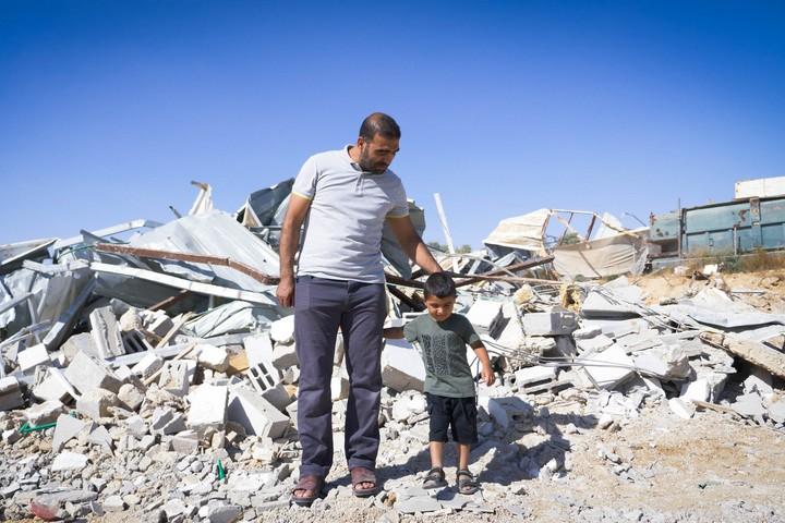 מוחמד ובנו, ליד הריסות באל זרנוג (צילום: רחל שור)