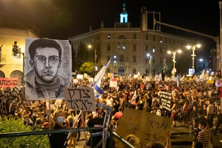 איש לא ביקש מהמפגינים נגד הכיבוש להוריד שלטים או לזוז. מפגין עומד עם דגל ישראל וציור של איאד אלחלאק (צילום: אורן זיו)
