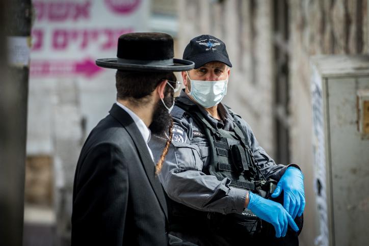 חלק מהשיח הניאו-ליברלי בהוא להאשים את העניים. שוטר וחרדי במאה שערים בירושלים (צילום: יונתן זינדל / פלאש 90)