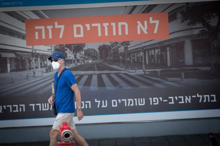 """הסלוגן """"אם לא נהיה בסדר, נהיה בסגר"""" הוא איום מפורש על האזרחים. אזרח בתל אביב שחט אזהרה מהקורונה (צילום: מרים אלסטר / פלאש 90)"""