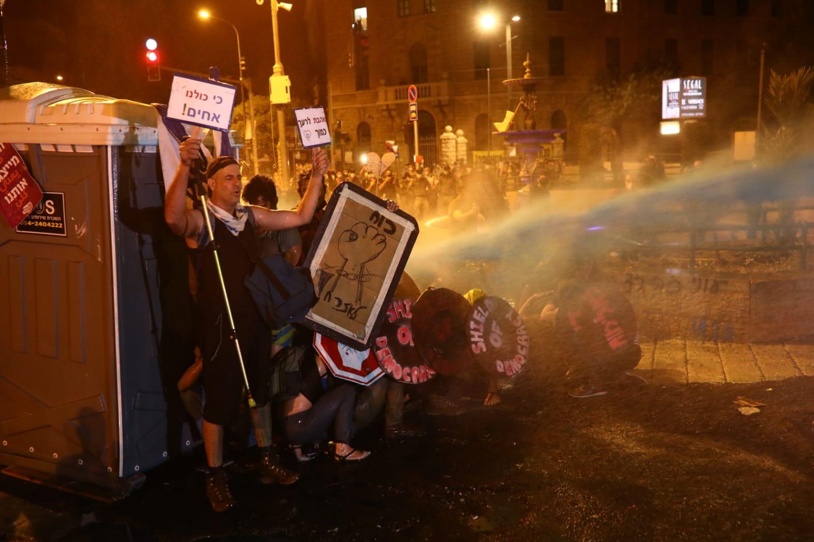 """מפגינים סופגים סילון מים ממכת""""זית, 25 ביולי 2020 (צילום: אורן זיו)"""