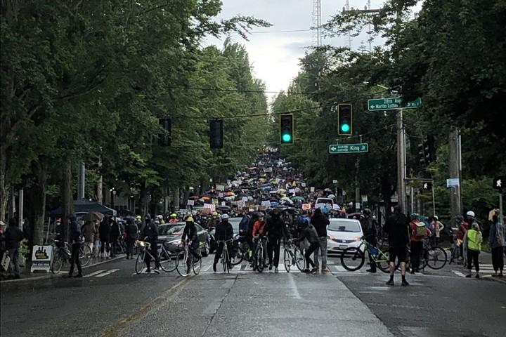 """לפחות במקרה אחד, רוכבי האופניים מנעו מנהג לדהור לתוך קהל המפגינים. """"בריגדת האופניים של סיאטל"""" על רקע הפגנה בעיר (צילום: ג'ן מרלו)"""