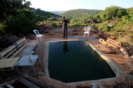 שכן הזעיק אותו ואמר לו: עובדים על האדמה שלך. עאמר אבו חיג'לה ליד הבריכה שנבנתה על אדמתו (צילום: אחמד אלבאז / אקטיבסטילס)