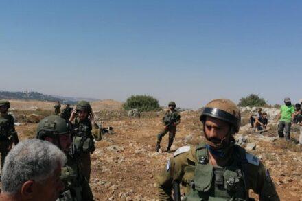 חיילים באדמות הכפר בתיר אחרי שהוזעקו בידי תושבי הכפר. המתנחל ליאור טל בחולצה הירוקה מימין (צילום: ע'סאן עליאן)
