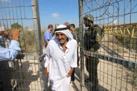 """""""זכותו של כל אדם להגיע לאדמה שלו, זו צריכה להיות הנחת היסוד"""". פלסטיני חוצה שער חלקאי בגדר ליד הכפר פלאמיה (צילום: אחמד אלבאז / אקטיבסטילס)"""