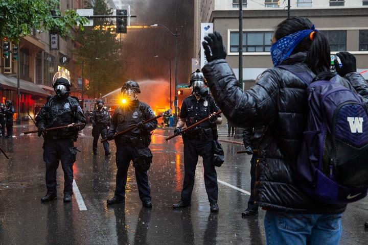 המטרה היא לאפשר למפגינים למחות בראש שקט. מפגינה מול שוטרים בסיאטל (צילום: קלי קליין CC BY NC ND 2.0)
