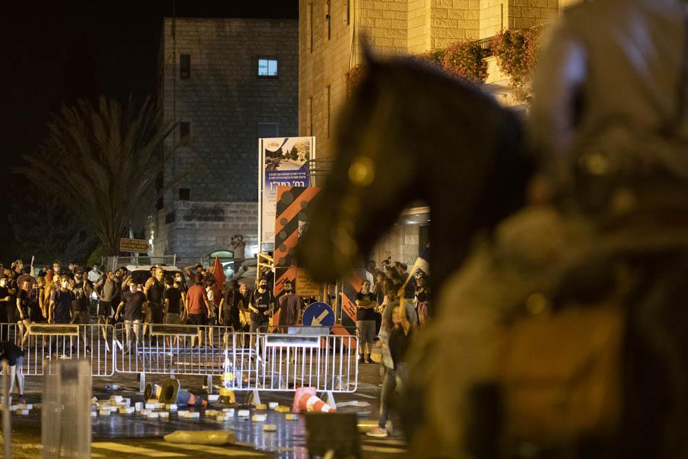מפגינים מול שוטרים בכיכר פריז, סמוך למעון ראש הממשלה בירושלים, בעזרת תותח מים, 15 ביולי 2020. (צילום: אורן זיו)