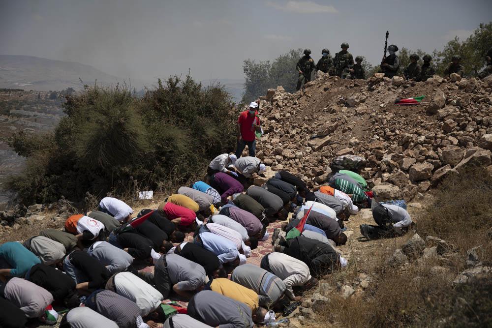 חיילים עומדים על תלולית העפר שהקים הצבא כדי למנוע גישה לאדמות עליהן הוקם מאחז, במהלך תפילת מחאה בעסירה א-שמאלייה, 10 ביולי 2020 (צילום: אורן זיו)