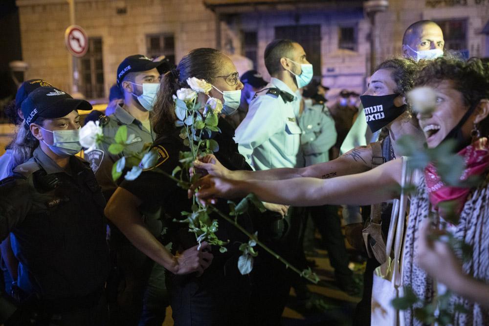 מפגינים מנסים לחק פרחים לשוטרים, במהלך הפגנה מול מעון ראש הממשלה, 23 ביולי 2020 (צילום: אורן זיו)