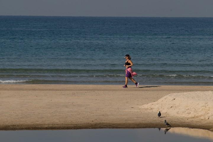 אישה רצה על החוף בהרצליה (צילום: נתי שוחט / פלאש90)