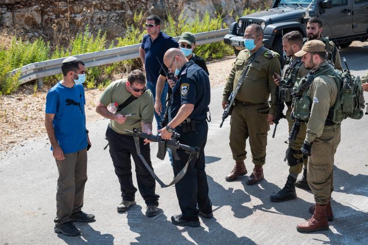 שוטרים וחיילים בוחנים נשק באירוע בו מתנחלים ירו בפלסטינים ליד הכפר בידיא, 5 ביולי 2020 (צילום: שריה דיאמנט\פלאש 90)