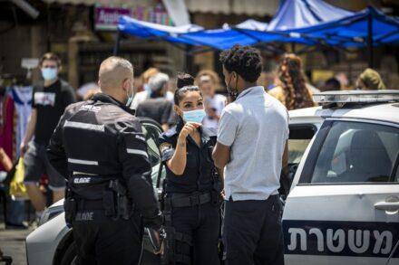 אדם מקבל קנס על אי עטיית מסיכה בירושלים, ב-7 ביולי 2020 (צילום: אוליבייה פיטוסי / פלאש90)