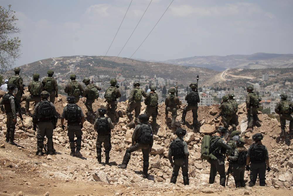 חיילים ושוטרי מג״ב עומדים על תלולית העפר שהקים הצבא כדי למנוע גישה לאזור מאחז שהקימו מתנחלים באדמות העירייה עסירה א-שמאלייה, 10 ביולי 2020 (צילום: אורן זיו)