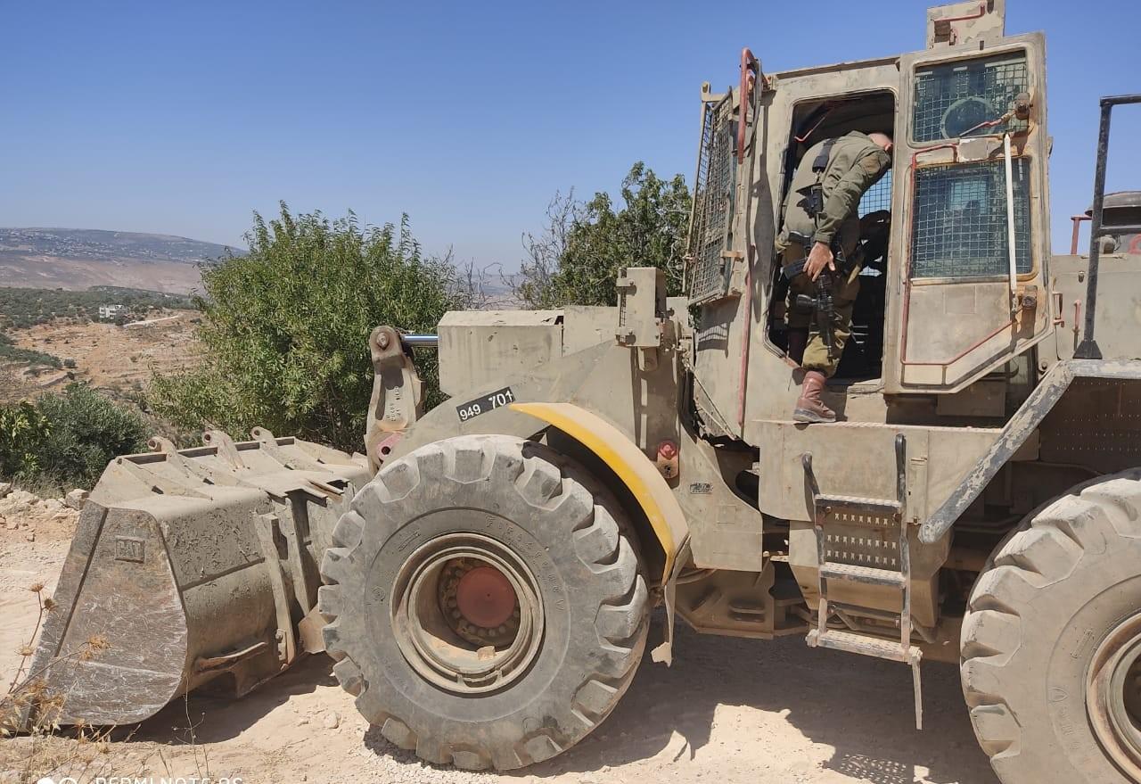 דחפור צבאי עובד על הקמת תלולית עפר בעיירה עסירה א-שמלייה (צילום: חאזם יוסף יאסין)