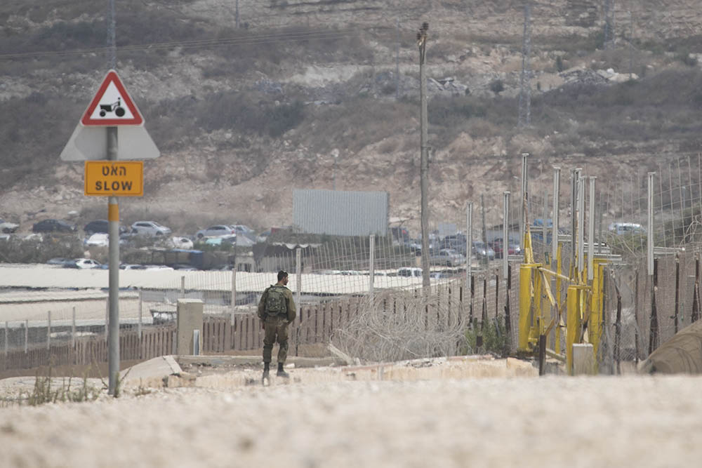 חייל עומד סמוך לנקודה בה פלסטינים עברו את הגדר בכפר פרעון שליד טול כרם (צילום: אחמד אל באז ואורן זיו)