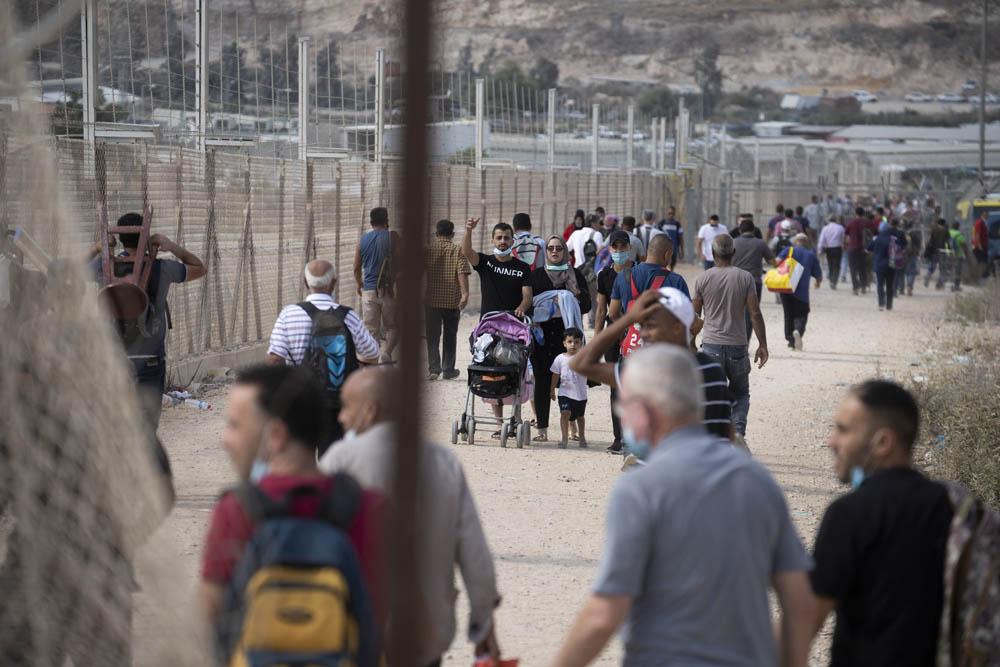 פלסטינים עוברים את הגדר בדרכם לים, כשפועלים חוזרים מעבודה בישראל לגדה, ליד טול כרם (צילום: אורן זיו)