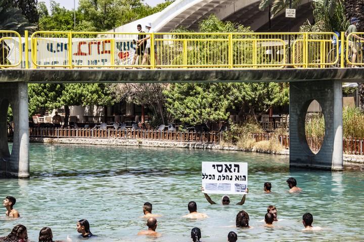 הפעילים למען שחרור האסי רוחצים בנחל בתוך שטח הקיבוץ (צילום: מתי מילשטיין)