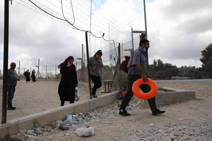 פלסטינים מהגדה עוברים את גדר ההפרדה בדרכם לים, ב-10 באוגוסט 2020 (צילום: אחמד אל-באז ואורן זיו)