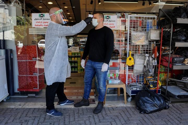 מקבלים מאות פניות, אבל אין מוקד בערבית שיענה להם. לקוח ומוכר בחנות בדיר אלאסד (צילום: באסל עווידאת / פלאש 90)