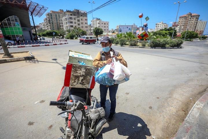 אדם נושא מצרכים במהלך הסגר בעזה, ב-27 באוגוסט 2020 (צילום: מוחמד זאנון / אקטיבסטילס)