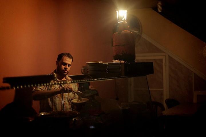 פלסטיני משתמש במנורת גז במסעדה שלו בזמן הפסקת חשמל ברצועת עזה, ב-2013 (צילום: עימאד נאסר / פלאש90)