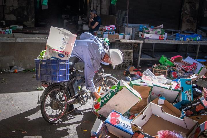 אדם מחפש פירות וירקות על הרצפה בשוק ברמלה, ב-17 ביולי 2020 (צילום: יוסי אלוני / פלאש90)