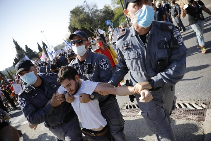 תנו לנו סיבה להאמין שאתם דואגים לנו ונציית. שוטרים מפנים מפגין מול הכנסת (אוליבייה פיטוסי / פלאש 90)