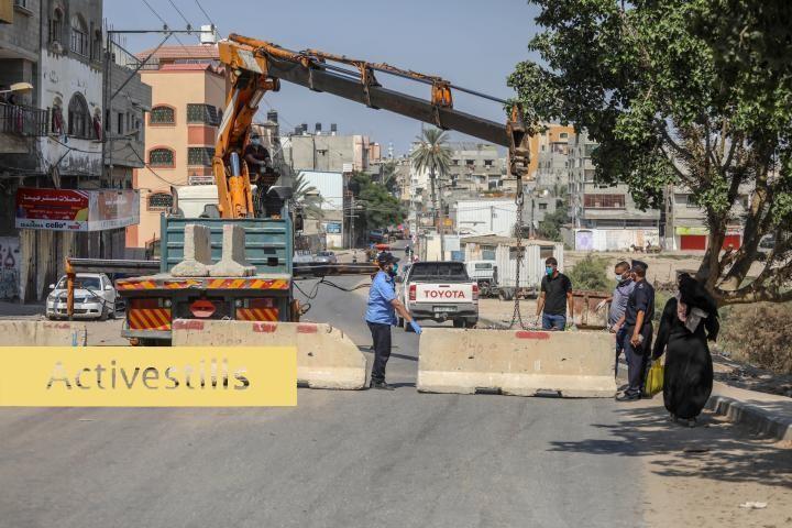 שוטרים פלסטינים שומרים על מחסומי בטון שהוצבו כחלק מהסגר הכללי שהוטל על הרצועה בעקבות התפרצות הקורונה, ב-27 באוגוסט 2020 (צילום: מוחמד זאנון / אקטיבסטילס)