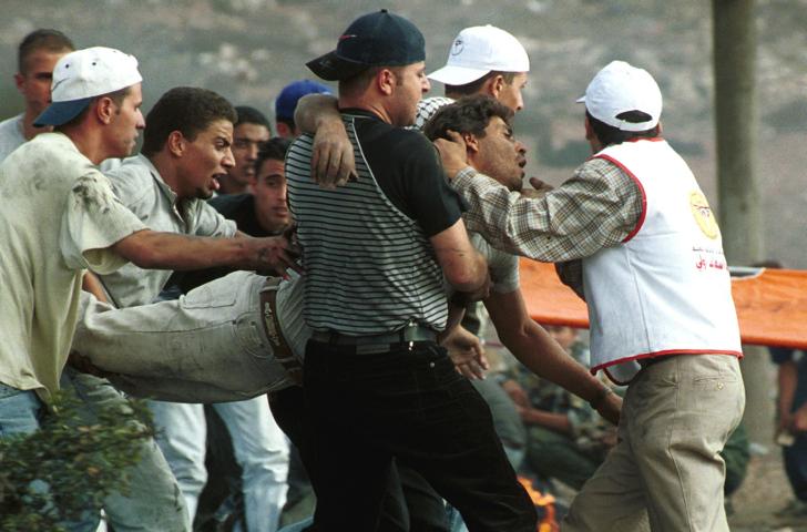 """פלסטיני פצוע בעימות עם המשטרה בתחילת האינתיפאדה השנייה בצומת איו""""ש (צילום: יולה מונקוב, פלאש90)"""