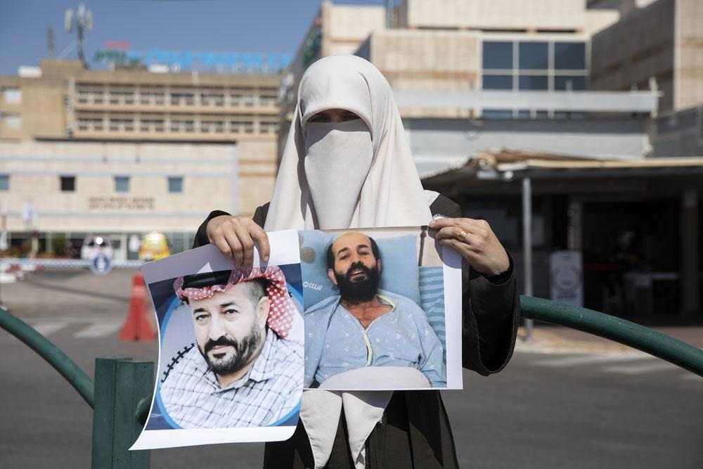 תגריד, אשתו של של שובת הרעב מאהר אלאח׳רס, מחוץ בלית החולים קפלן עם צילום של בעלה לפני השביתה ובמהלכה. (צילום: אורן זיו)