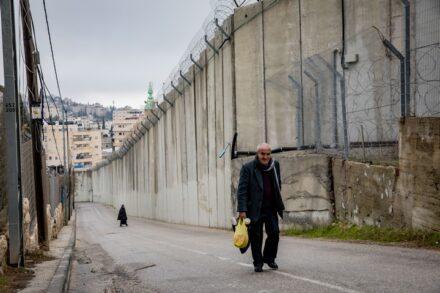 פלסטיני הולך ליד גדר ההפרדה באבו דיס, ב-2 בפברואר 2020 (צילום: אוליבייה פיטוסי / פלאש909