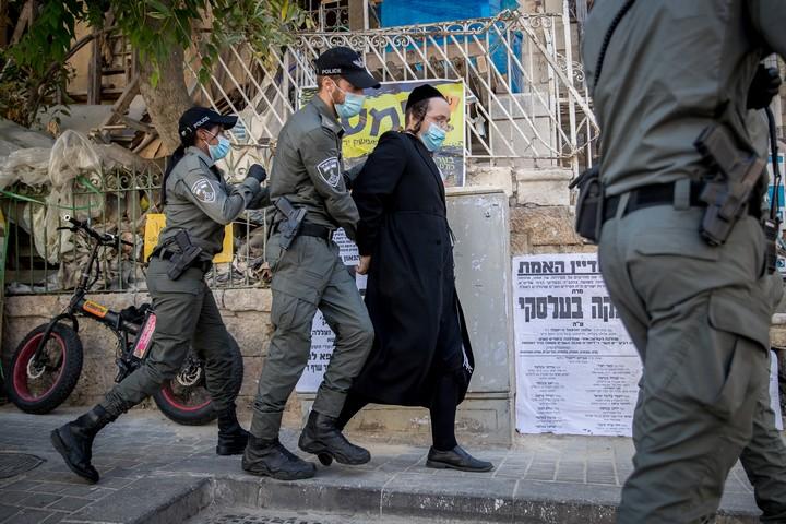 שוטרים עוצרים חרדי בפשיטה על בית כנסת בשכונת גאולה בירושלים שנפתח בניגוד לתקנות הקורונה, ב-14 באוקטובר 2020 (צילום: יונתן זינדל / פלאש90)