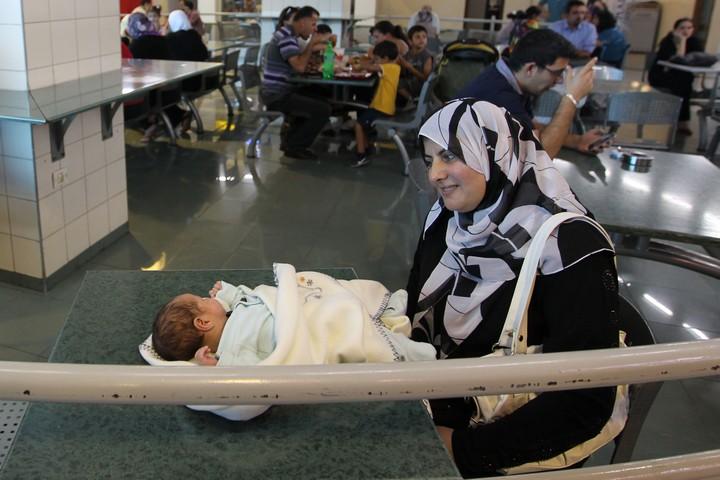 """""""לא ייתכן שהתושב או התושבת הפלסטינים ישלמו על כך את המחיר"""". אם ותינוק במרכז קניות ברמאללה (נתי שוחט / פלאש 90)"""
