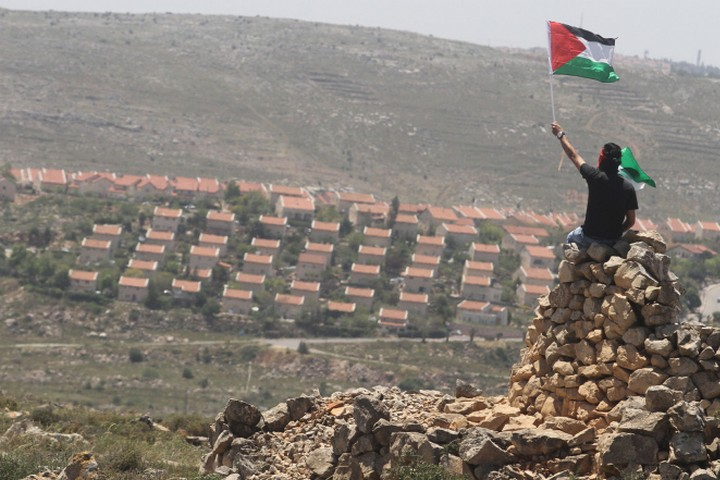 מירון בנבנישתי כתב שהסיפוח הוא בלתי הפיך. הוא צדק. מפגין פלסטיני על רקע התנחלות עפרה בגדה המערבית (צילום: עיסאם רימאווי / פלאש 90)
