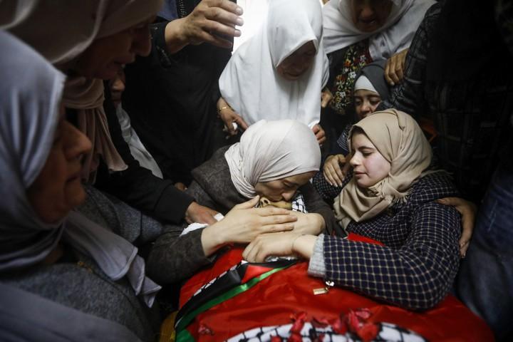 החייל ירה בו ששה כדורים בזמן שניסה לברוח מהצומת. קרובי משפחתו של אחמד מנאסרה ליד גופתו (צילום: ויסאם השלמון / פלאש 90)