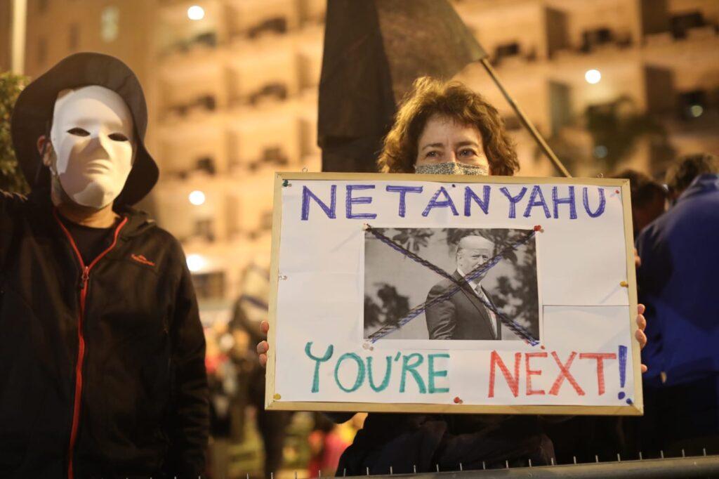 אלתרה שלט לפני שיצאה מהבית. מפגינה הערב בבלפור אחרי ההודעה על הניצחון של ביידן (צילום: אורן זיו)