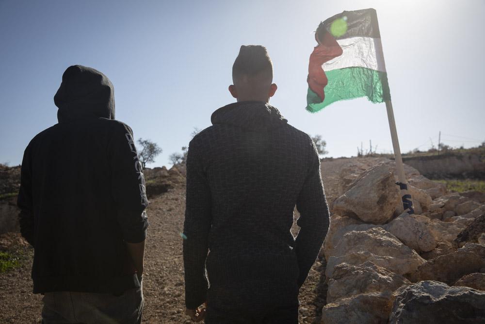 בנקודה שבה עלי אבו עליא נורה למוות מתנוסס דגל פלסטין. באסם ואחמד, אחיו וחברו של עלי, ליד מקום הירי באל-מוע'ייר (צילום: אורן זיו)