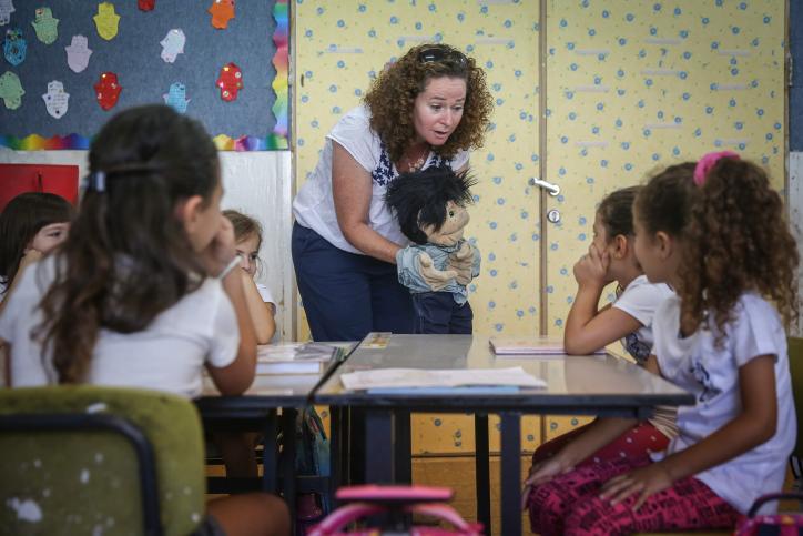 """ביפן רק שליש מהשעות של המורים מוקדשות להוראה. מורה מקבלת תלמידי כיתה א בבי""""ס בירושלים (צילום: הדס פרוש / פלאש 90)"""