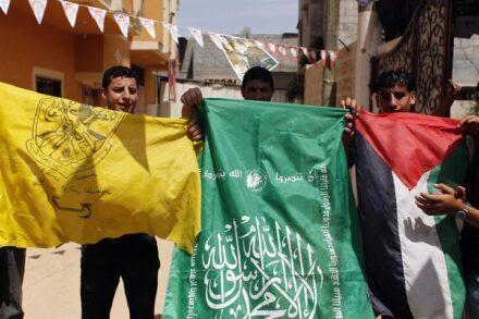"""מפגינים פלסטינים מניפים דגלי פת""""ח, חמאס ודגל פלסטין בתמיכה בפיוס לאומי, בחאן יונס ברצועת עזה, ב-29 במאי 2014 (צילום: עבד רחים חטיב / פלאש90)"""