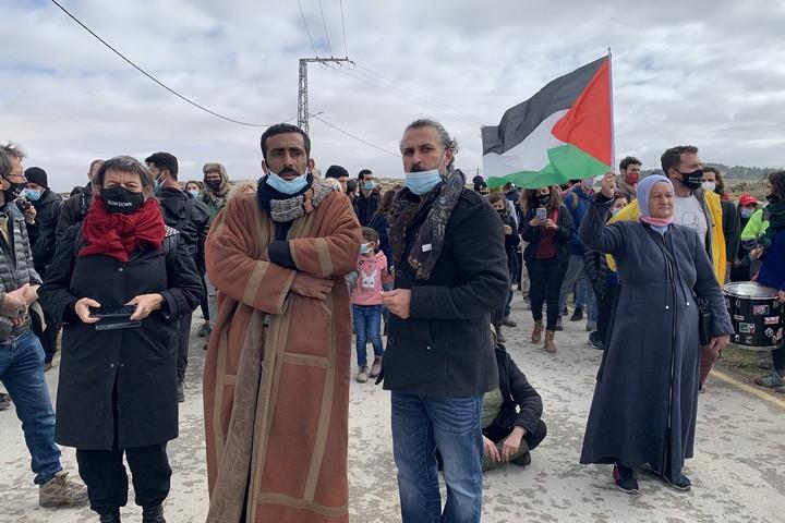 אדם רביע מלוחמים לשלום (במרכז) עם המפגינים בכניסה לכפר א-טוואני (חגי מטר)