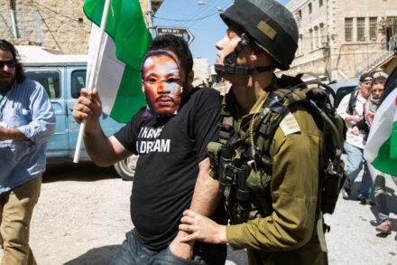 חיילים עוצרים את עיסא אמרו, עם מסכה של מרתין לותר קינג, ברחוב השוהדא בחברון בזמן ביקור אובמה בישראל, מרץ 2013 (צילום: אקטיבסטילס)