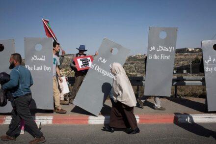 עד שלא תמומשנה כל הזכויות של הפלסטינים, הן כפרטים והן כקיבוץ לאומי, לא יושג קץ לסכסוך. אישה פלסטינית חולפת ליד מיצג חומה בהפגנה במחסום המנהרות (אורן זיו / אקטיבסטילס)