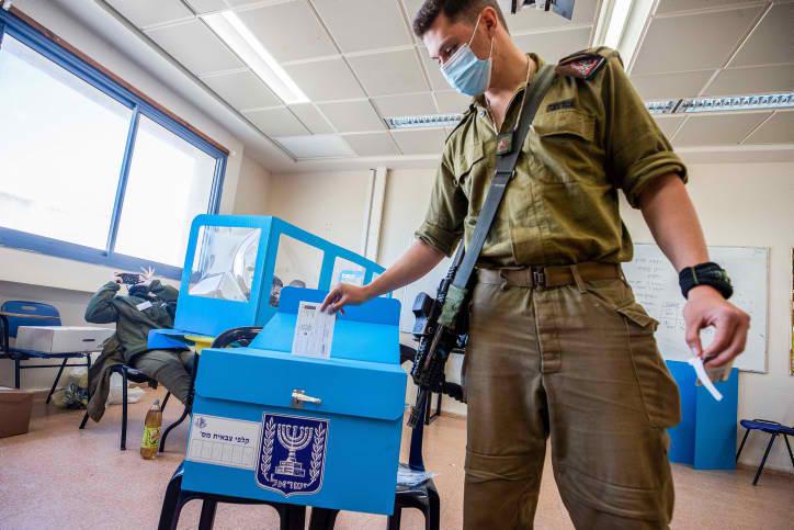 חמישה חיילים שמחליטים לא להעביר פלסטיני במחסום זו לא דמוקרטיה. חייל מצביע בקלפי בבסיס צבאי בהצבעה מוקדמת בבחירות במארס 2012 (צילום: פלאש 90)