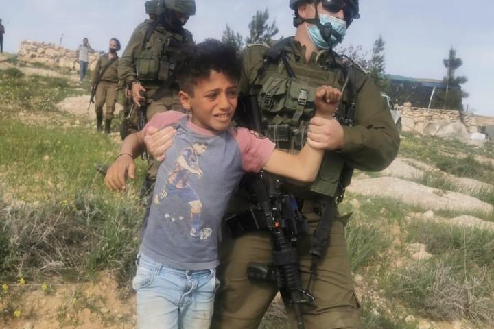 """""""תסתכלו על עצמכם"""". חיילים עוצרים ילדים בכפר רכיז, דרום הר חברון (צילום: נאסר נוואג'עה, בצלם)"""