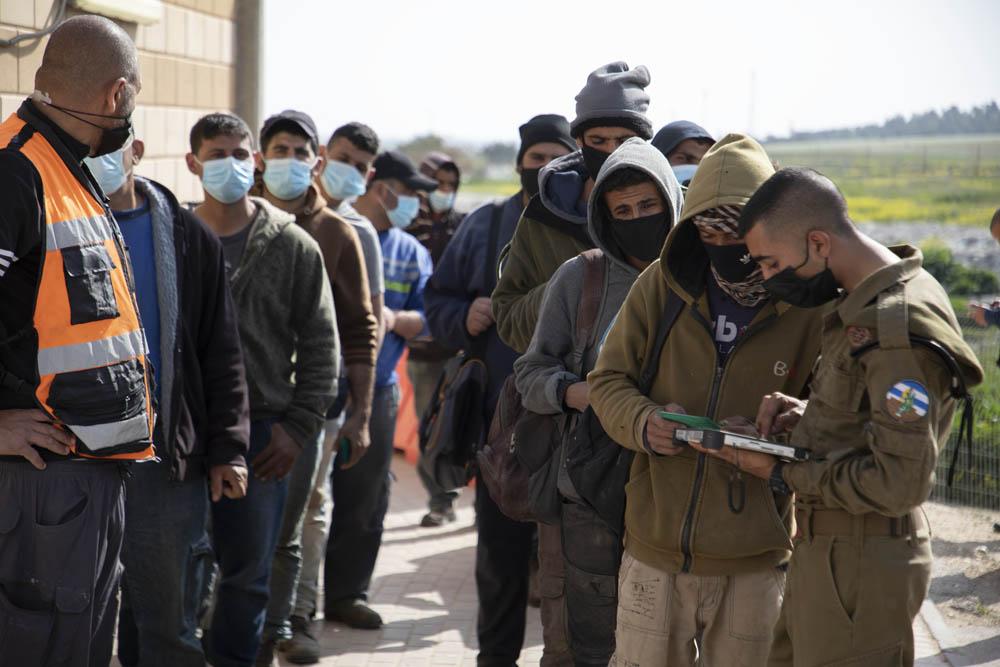 עובדים פלסטינים מהגדה המערבית ממתינים בתור כדי להתחסן במחסום מיתר, 8 במרץ 2021 (צילום: אורן זיו)