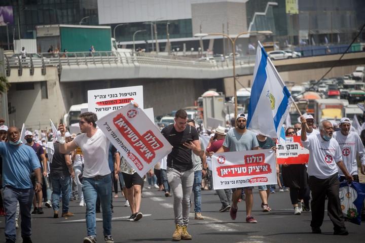 """נכי צה""""ל מפגינים מחוץ למשרד הביטחון בתל אביב, אחרי שאיציק סעידיאן הצית את עצמו מול משרד השיקום, ב-18 באפריל 2021 (צילום: מרים אלסטר / פלאש90)"""
