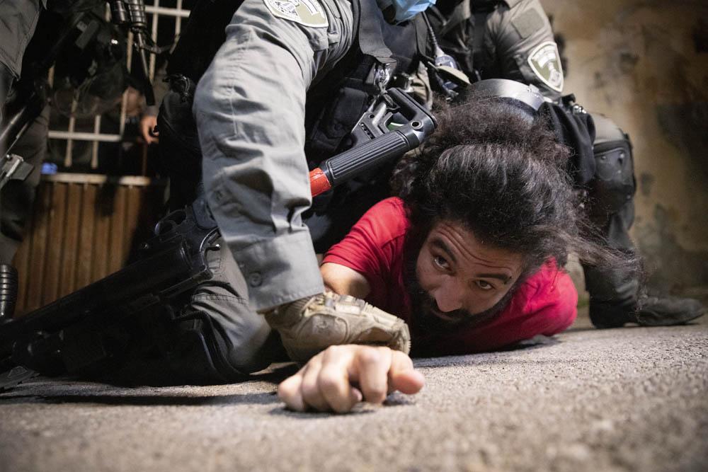"""""""זו לא הפגנה, אבל גם אם כן, זכותנו להיות כאן"""". שוטרים עוצרים צעיר פלסטיני בשכונת שייח׳ ג'ראח שבמזרח ירושלים, 4 במאי 2021 (צילום: אורן זיו)"""